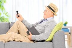 Emissão do homem superior sms através do telefone celular em casa foto de stock royalty free
