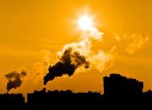 Emissões da central energética sob a cidade. Imagens de Stock