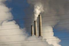 Emissões que aumentam de uma estação a carvão do central elétrica com fios elétricos da distribuição da grade no primeiro plano imagem de stock royalty free