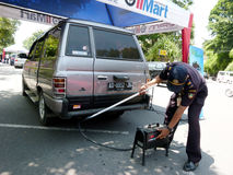 Emission tests. Transportation department officials conduct emission tests on vehicles in the streets of the city of Solo, Central Java, Indonesia Stock Image