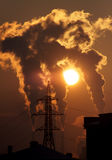 Emissions. High voltage tower and power plant during sunset Royalty Free Stock Photography