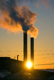 Emissions from plant pipe against setting sun Stock Photography