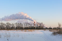 Emissions into the sky from thermal power plant. Emissions into the clear blue winter atmosphere from thermal power plant chimney Stock Photo