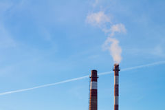 Emissions of thermal power from plant`s chimney pipes on blue sky background. Royalty Free Stock Photo