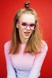 Emitonal bonito joven que presenta al adolescente en el fondo rojo brillante, concepto sonriente feliz de la gente de la forma de Fotos de archivo libres de regalías