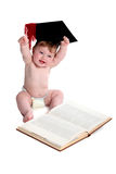 Emma with graduation hat. Beautiful baby girl with graduation hat,sitting at a textbook and throwing her hands triumphantly in the air royalty free stock photography