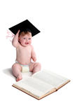 Emma with graduation hat. Beautiful baby girl with graduation hat,sitting at a textbook and throwing her hands triumphantly in the air stock photo
