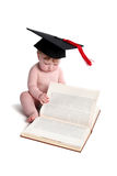 Emma with graduation hat. Beautiful baby girl with graduation hat,sitting,paging through a textbook royalty free stock image