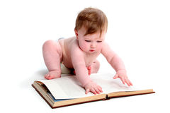 Emma with textbook. Baby girl paging through a textbook isolated on a white background royalty free stock photos