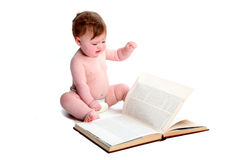 Emma with textbook. Baby girl paging through a textbook isolated on a white background stock photos