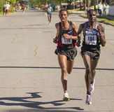 Emmanual Bett от Кении водит общий победителя Belete Assefa Эфиопии по мере того как они ломают далеко от пакета. Стоковые Изображения