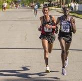 Emmanual Bett du Kenya mène le gagnant global Belete Assefa de l'Ethiopie pendant qu'ils se cassent à partir du paquet. Images stock
