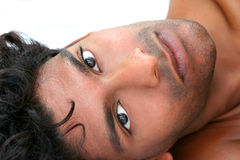Emmanuel 15. Handsome young exotic man, lying in bed Royalty Free Stock Image