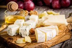 Emmental, Camembert, Parmesan, blue cheese with bread sticks, nuts, honey and grapes Royalty Free Stock Photos