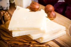 Emmental cheese close-up with nuts on a wooden board Royalty Free Stock Photo