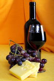Emmental cheese with wine and grapes Stock Images