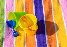 2 emmers en schoppen van het kind` s zand op een gestreepte strandhanddoek Stock Afbeeldingen