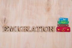 Emmigration, слово в абстрактных деревянных письмах Поверхность предпосылки деревянная и куча чемоданов Стоковое Изображение RF