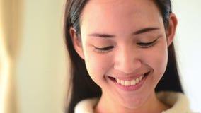 Emoção asiática da cara do sorriso da mulher e tabuleta tocante do computador