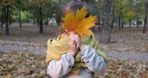 A emoção da felicidade, criança fêmea cobre sua cara com a folha do amarelo do bordo e sorriso na câmera na natureza dentro filme