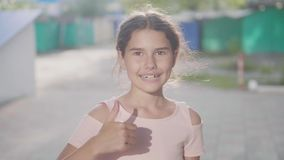 A emoção da menina mostra os polegares do estilo de vida da mão do vídeo de movimento sim lento do gesto acima fora vídeos de arquivo