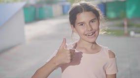A emoção da menina mostra os polegares da mão do vídeo de movimento sim lento do gesto acima do estilo de vida fora filme