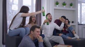 A emoção, fãs que olham o fósforo de futebol na tevê com excitamento e exulta então na vitória que senta-se no sofá com a video estoque