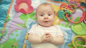 Emoção feliz do bebê Retrato da criança bonito que encontra-se para trás A criança doce aprecia o mundo vídeos de arquivo