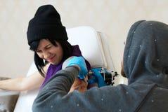 Emoções de uma menina ao fazer um tatuagem Fotografia de Stock Royalty Free