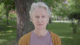 Emo??es diferentes da mulher adulta com cabelo cinzento no parque bonito Av? madura ador?vel que descansa em um ensolarado vídeos de arquivo