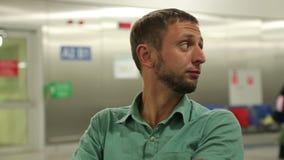 Emoções do voo de espera do homem ansioso no aeroporto, olhando ao redor nervosamente vídeos de arquivo