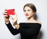 Emoções, expressões e conceito dos povos - jovem mulher de sorriso feliz que veste o vestido preto que toma o selfie com smartpho fotos de stock