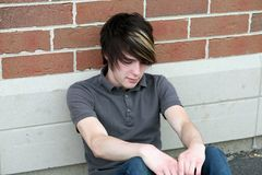 Emo Boy. Sad teen boy with cool hair sitting outside school Royalty Free Stock Images