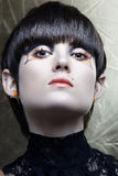 Emo girl with avantgard make-up. Emo girl with straight fringe bob and alternative make-up, piercings on lip and ear from 16bit RAW stock photo