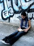 Emo girl reading. Near a graffiti wall Royalty Free Stock Photography
