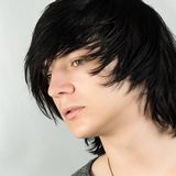 Emo hairstyle for boys. Close-up portrait of handsome teenage boy with black hair emo hairstyle on white background royalty free stock images