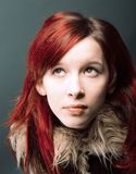 Emo look girl with red hair. On gray background royalty free stock image
