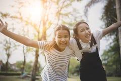 Emoción asiática alegre de la felicidad del adolescente dos en parque público Imagenes de archivo