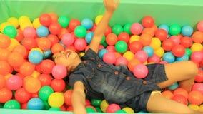 Emoción de la felicidad de los niños en colorido en piscina de la bola almacen de video
