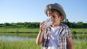 Emoción de la felicidad, retrato del niño sonriente que bebe el agua mineral del vidrio en aire abierto metrajes