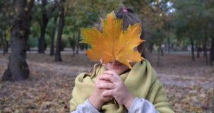 Emoción feliz, niño femenino del retrato con la hoja del amarillo del arce que sonríe en cámara en la naturaleza en otoño almacen de metraje de vídeo