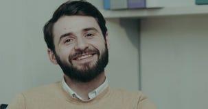 Emoción real del primer del trabajador de los hombres de la oficina que mira derecho a la cámara y a la sonrisa metrajes