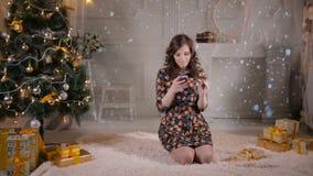 Emocional atractivo usando smartphone con la tarjeta de crédito para los regalos de compra en línea en la Navidad cerca del árbol metrajes