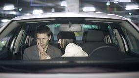 Emociones de un par joven en el coche en el estacionamiento subterráneo almacen de video
