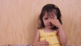 Emociones de un pequeño niño Niña en un vestido amarillo Retrato de una muchacha hermosa almacen de metraje de vídeo