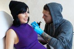Emociones de una muchacha mientras que hace un tatuaje Fotos de archivo libres de regalías