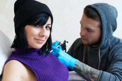 Emociones de una muchacha mientras que hace un tatuaje Imagen de archivo libre de regalías