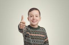 emociones Muchacho sonriente que mira la cámara que detiene su finger Imagen de archivo libre de regalías
