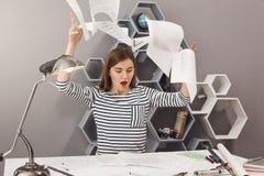 Emociones negativas Retrato de los papeles que lanzan del arquitecto de sexo femenino apuesto joven enojado lejos, estando enojad imágenes de archivo libres de regalías