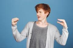 Emociones positivas Individuo atractivo joven divertido del jengibre en camiseta gris debajo de la rebeca que habla con sus manos Fotos de archivo